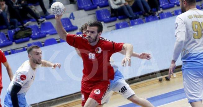 Lojtari po gjuan topin kurse tre lojtarë kundërshtarë po mundohen t'a ndalojnë.