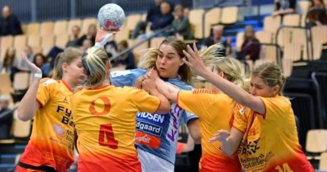 Në foto shihet kapitenia e Kombëtares së Kosovës, Leonora Demaj me top në dorë duke u munduar të largohet nga bllokimi i katër lojtareve kundërshtare.