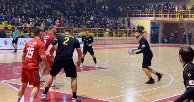 Lojtari ka topin në dorë dhe po vrapon, dy bashkëlojtarë të tij po i ndihmojnë duke u munduar t'i ndalojnë dy lojtarët kundërshtarë që mos t'a pengojnë gjuajtjen e lojtarit që ka topin.