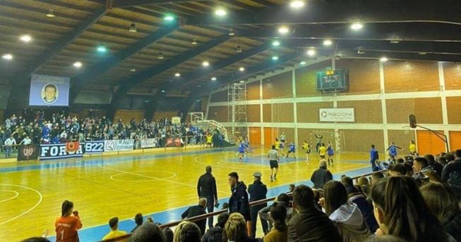 Në foto shihen lojtarët duke luajtur hendboll, dhe fotoja është shkrepur nga këndi i ulëseve të shikuesve.