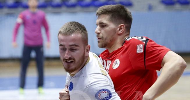 Në foto shihet një lojtar duke u munduar të largohet nga bllokimi i lojtarit kundërshtar.