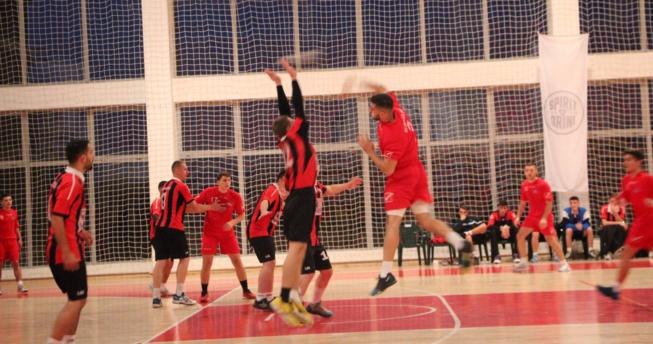 Në foto shihet një lojtar i cili është hedhur lartë dhe ka gjuajtur topin, përballë tij është një kundërshtar gjithashtu i hedhur lartë me duart e ngritura duke tentuar ta bllokojë gjuajtjen e tij, mbrapa të dy lojtarë ka lojtarë të dy ekipeve.