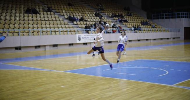 Në foto shihet një lojtare e cila në dorë ka topin dhe është hedhur lartë për të shënuar gol, kurse mbrapa është një bashkëlojtare e saj duke vrapuar.