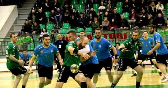 Lojtarit i ka rënë topi nga dora për shkak se kundërshtari i tij e ka kapur për fanellë me qëllim që t'a ndalojë lëvizjen e tij, kurse mbrapa tyre janë lojtarët e të dy ekipeve.