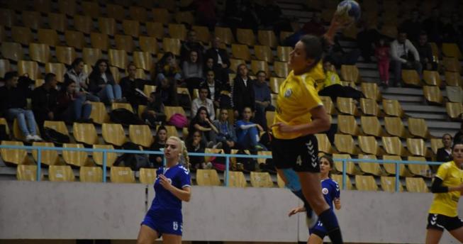 Në foto shihet një lojtare me top në dorë e cila është hedhur lartë për të shënuar në portë, mbrapa saj është një bashkëlojtare dhe dy lojtare të ekipit kundërshtar.