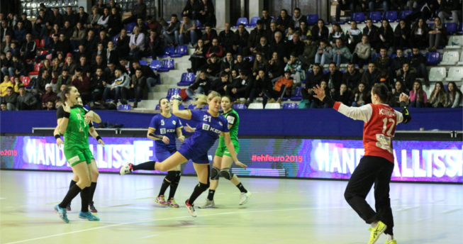 Në foto shihet një lojtare e Kombëtares sonë me top në dorë duke u munduar të shënojë gol, mbrapa saj është një bashkëlojtare, dhe tri lojtare te ekipit kundërshtar, kurse përballë ka portieren e ekipit kundërshtar duke tentuar ta bllokoje gjuajtjen e saj.