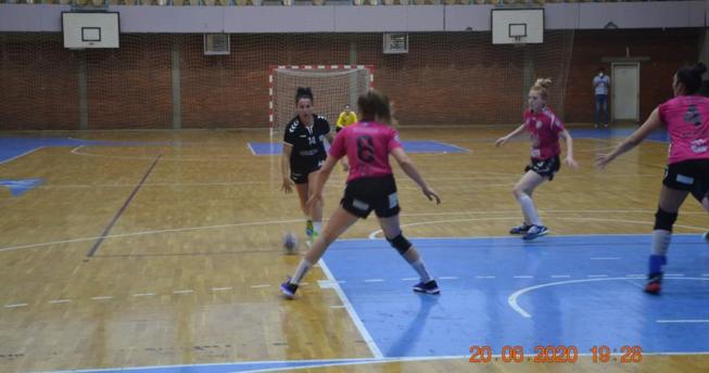 Një lojtare po vrapon drejt portës, kurse tri lojtare të ekipit kundërshtar janë në gjendje gatishmërie që t'a ndalojnë sulmin e saj.
