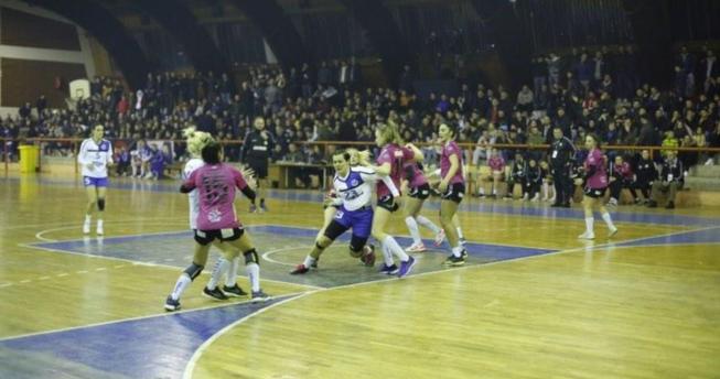 Një lojtare është duke vrapuar dhe është kapur nga dy kundërshtare me qëllim që t'a ndalojnë, dy kundërshtare tjera i ka mbrapa kurse përballë ka një bashkëlojtare e cila gjithashtu është kapur nga një kundërshtare.